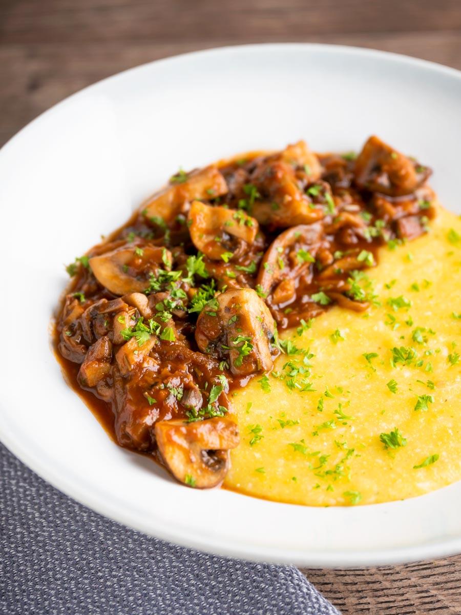 Super Chunky vegan mushroom ragu served with polenta and a parsley garnish