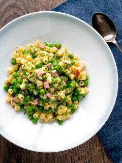 Pasta e piselli or pasta with peas and ham served in a white bowl.