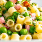 Pasta e piselli or pasta with peas and ham garnished with chopped parsley featuring a title overlay.