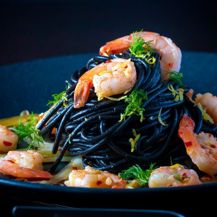 Prawn pasta with squid ink spaghetti fennel, lime zest and chilli served on a black plate.