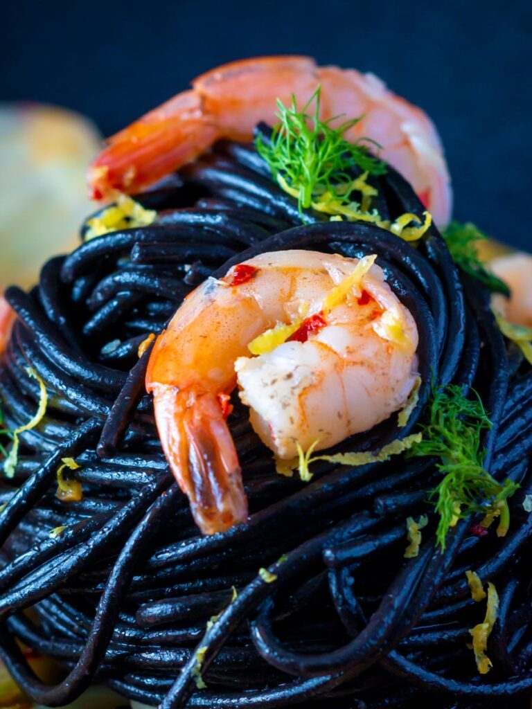 Close up prawn pasta with squid ink spaghetti fennel and chilli.
