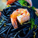 Close up prawn pasta with squid ink spaghetti fennel and chilli featuring a title overlay.