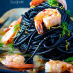 Prawn pasta with squid ink spaghetti fennel, lemon zest and chilli featuring a title overlay.