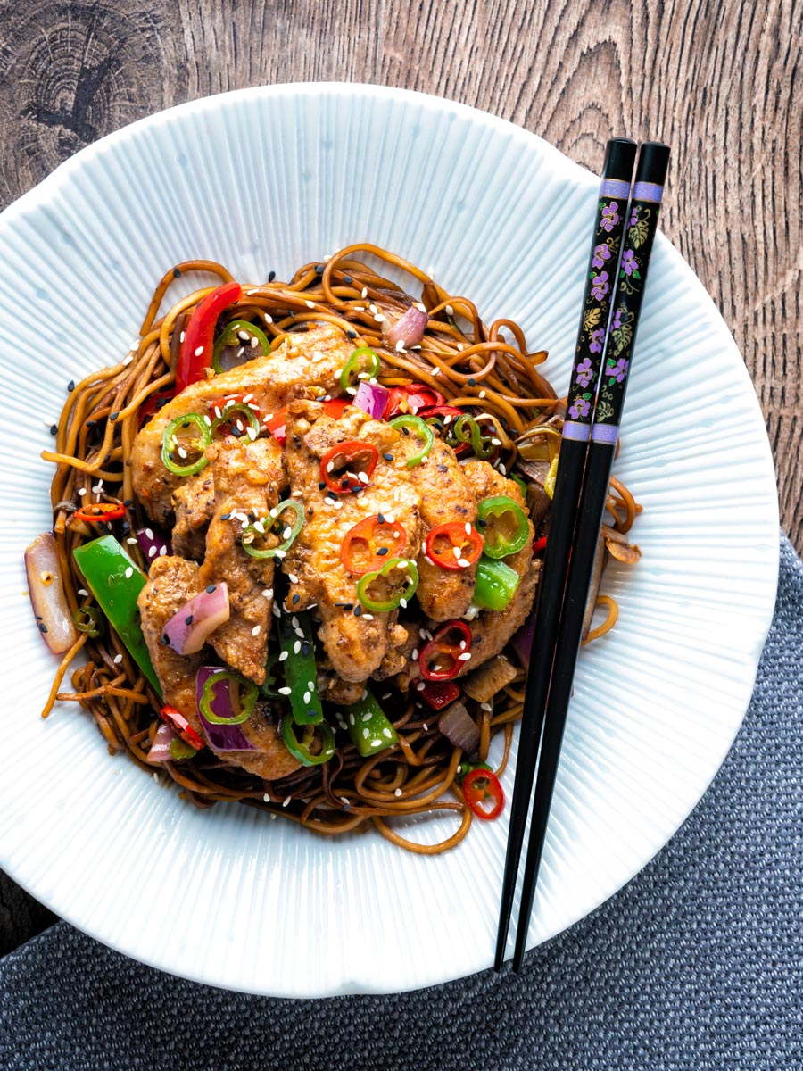Salt and chilli chicken served with peppers and onion on soy sauce noodles in a white bowl.