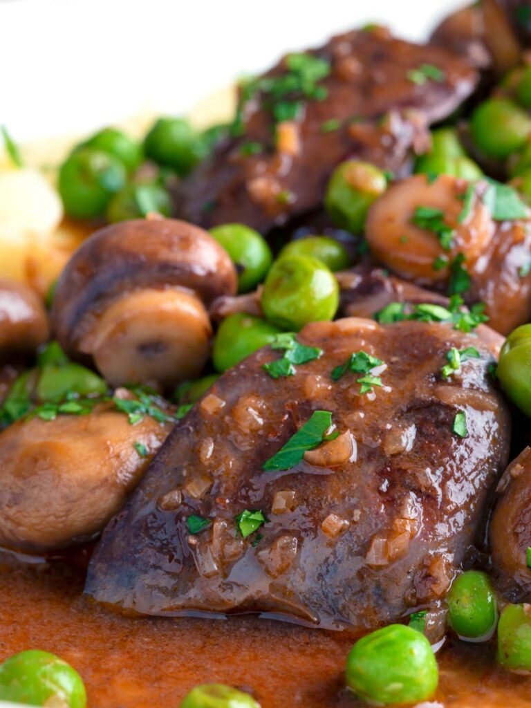 Close up chicken liver stew with button mushrooms and peas in red wine sauce.