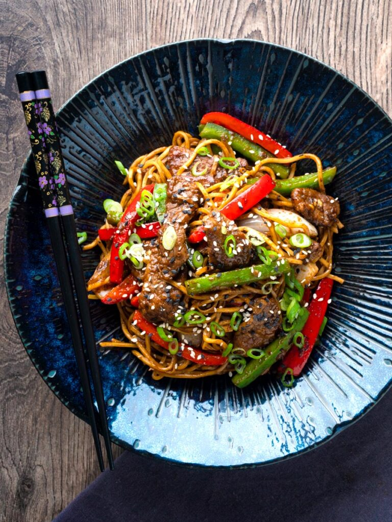 Overhead Szechuan beef stir fry with noodles and bell peppers served in a blue bowl