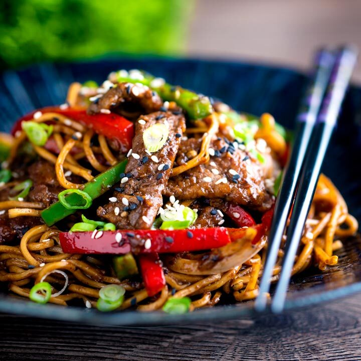 Szechuan beef stir fry with noodles and bell peppers served in a blue bowl with chopsticks.