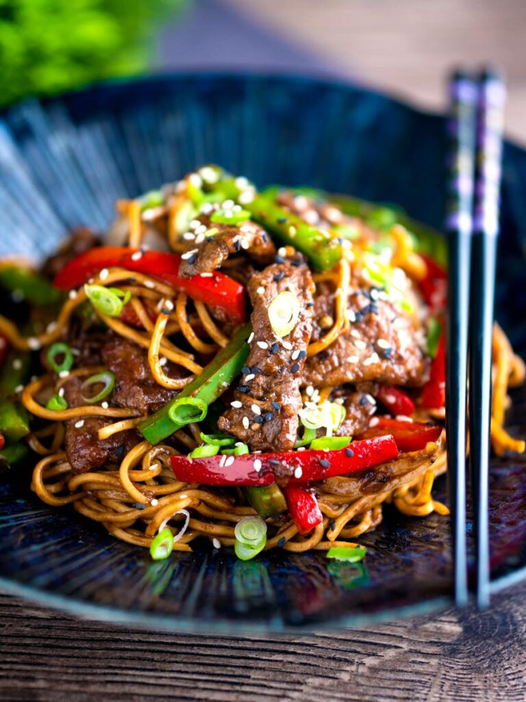 Szechuan beef stir fry with noodles and bell peppers served in a blue bowl.