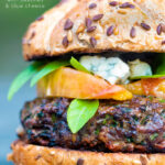 A venison burger served on a bun topped with blue cheese, gin cooked peaches & basil featuring a title overlay.