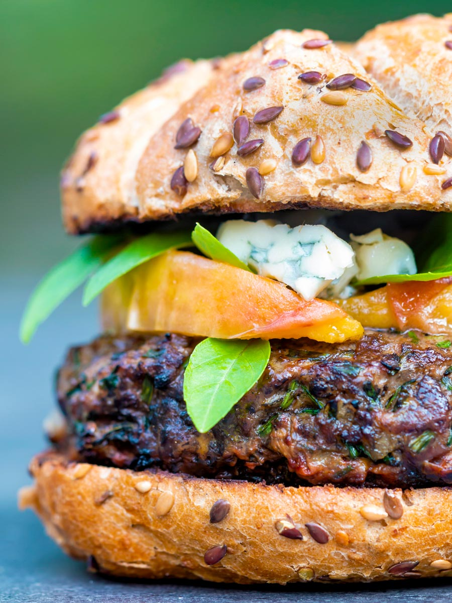 A venison burger served on a bun topped with blue cheese, gin cooked peaches & basil.