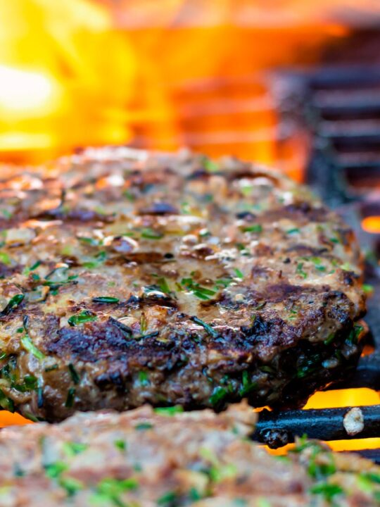 Venison burgers being cooked on a flaming barbecue.