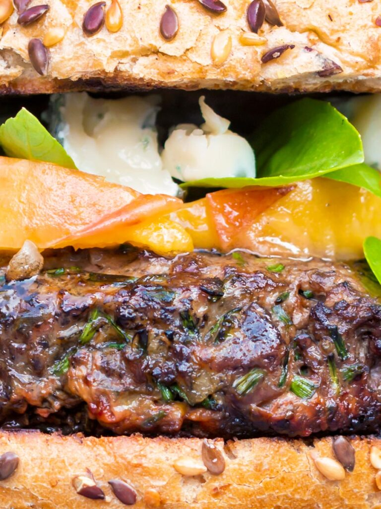 Close up venison burger served on a bun topped with blue cheese, peaches & basil.