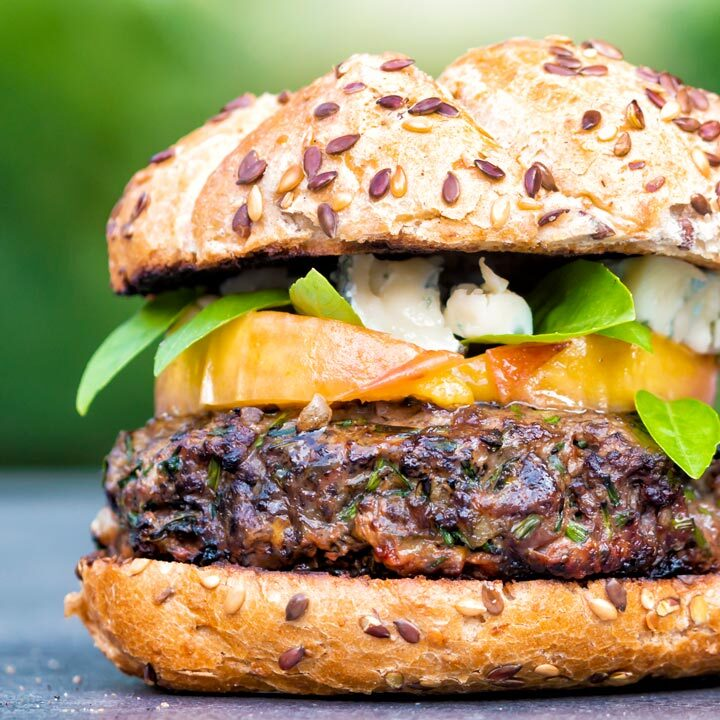 Venison burger served on a bun topped with blue cheese, peaches & basil.