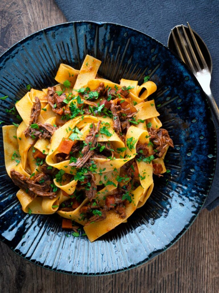 Overhead rich venison ragu sauce served with pappardelle pasta in a blue bowl.
