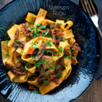 Overhead rich venison ragu sauce served with pappardelle pasta in a blue bowl featuring a title overlay.