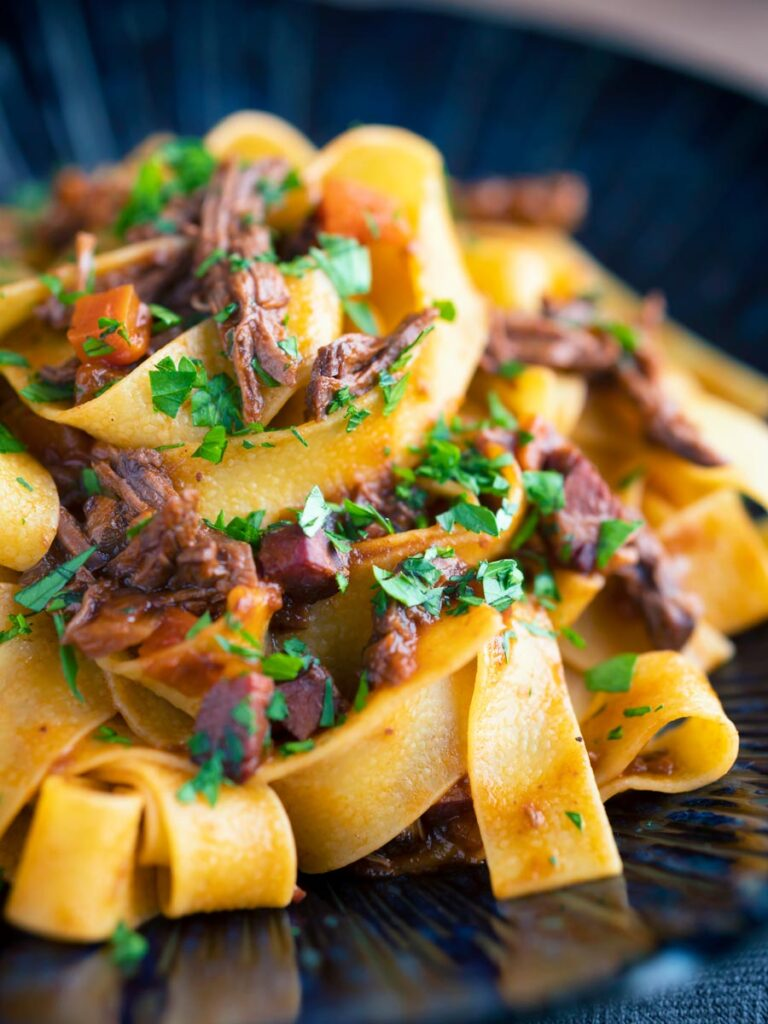 Venison ragu sauce served with pappardelle pasta in a blue bowl.