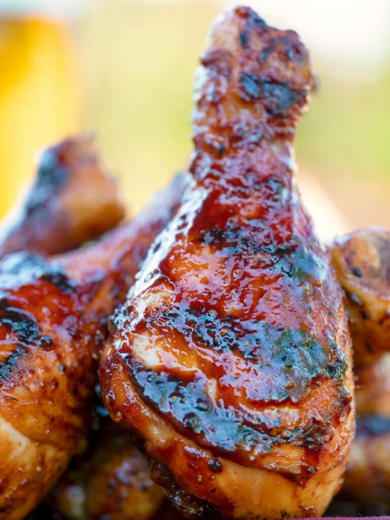 Close up bbq chicken drumsticks with a beer, paprika and honey glaze.