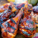 BBQ chicken drumsticks with a beer, paprika and honey glaze featuring a title overlay.