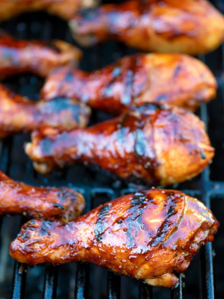 BBQ chicken drumsticks with a beer, paprika and honey glaze cooking on the grill.