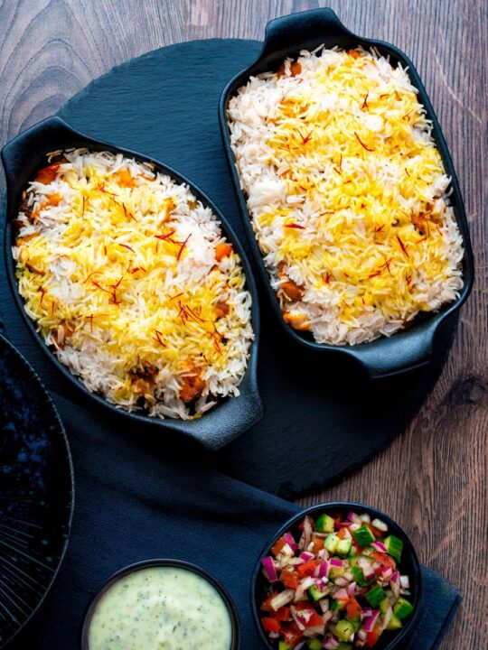 Overhead chicken tikka biryani served in stoneware bowls with kachumber salad and raita.