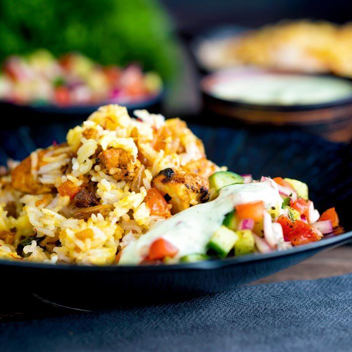 Spicy chicken tikka biryani served in a blue bowl with kachumber salad and mint raita.