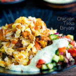 Chicken tikka biryani served in a bowl with kachumber salad and mint raita featuring a title overlay.