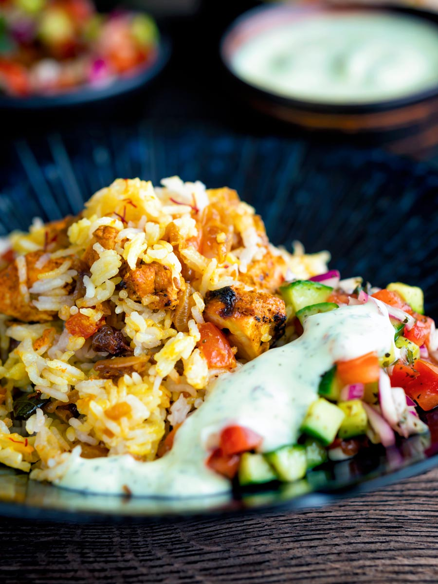 Chicken tikka biryani served in a bowl with kachumber salad and mint raita.