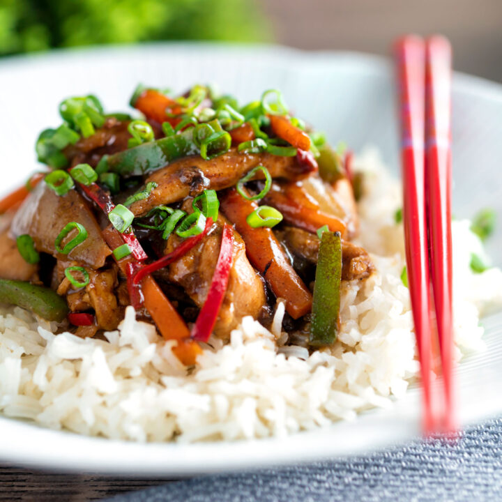 Chinese chicken with black bean sauce serve in a white bowl with rice and spring onions.