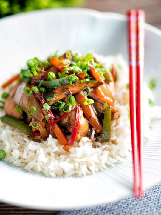 Chinese chicken with black bean sauce serve in a white bowl with rice and red chopsticks.