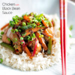 Chinese chicken with black bean sauce serve in a white bowl with rice and red chopsticks featuring a title overlay.