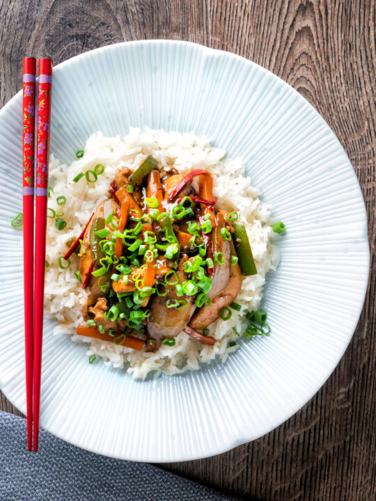 Overhead Chinese chicken with black bean sauce serve in a white bowl with rice.