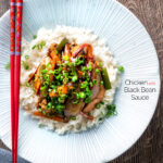 Overhead Chinese chicken with black bean sauce serve in a white bowl with rice featuring a title overlay.