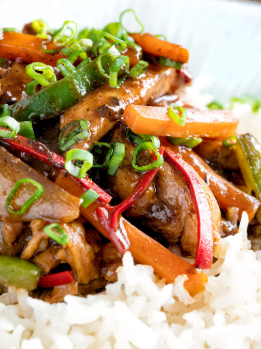 Close up Chinese chicken with black bean sauce serve in a white bowl with rice.