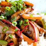 Close up Chinese chicken with black bean sauce serve in a white bowl with rice featuring a title overlay.