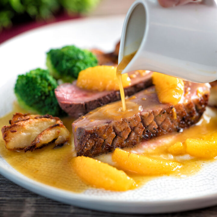 Orange sauce poured over a rosy pan fried duck breast with crispy skin.