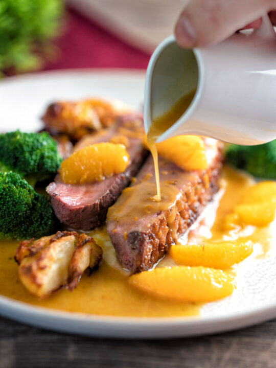 Orange sauce being poured over a rosy pan fried duck breast with crispy skin.
