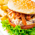 Halloumi burgers with harissa onions served with potato wedges featuring a title overlay.