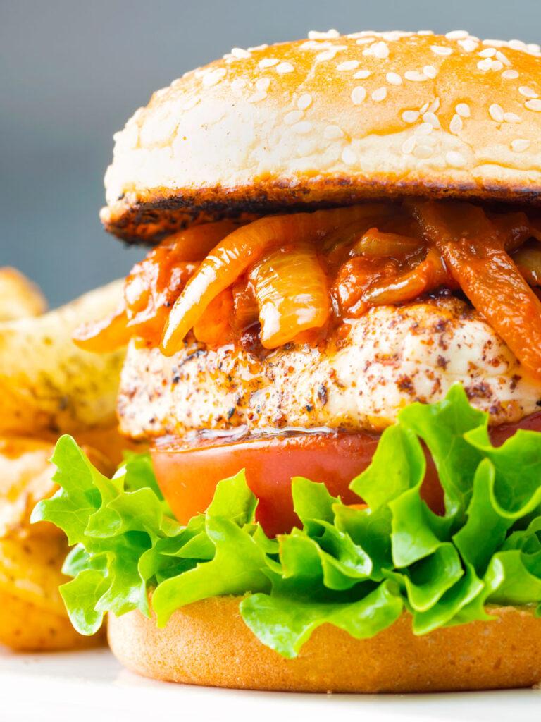 Halloumi burger with harissa onions, tomato & lettuce on a sesame seed bun.