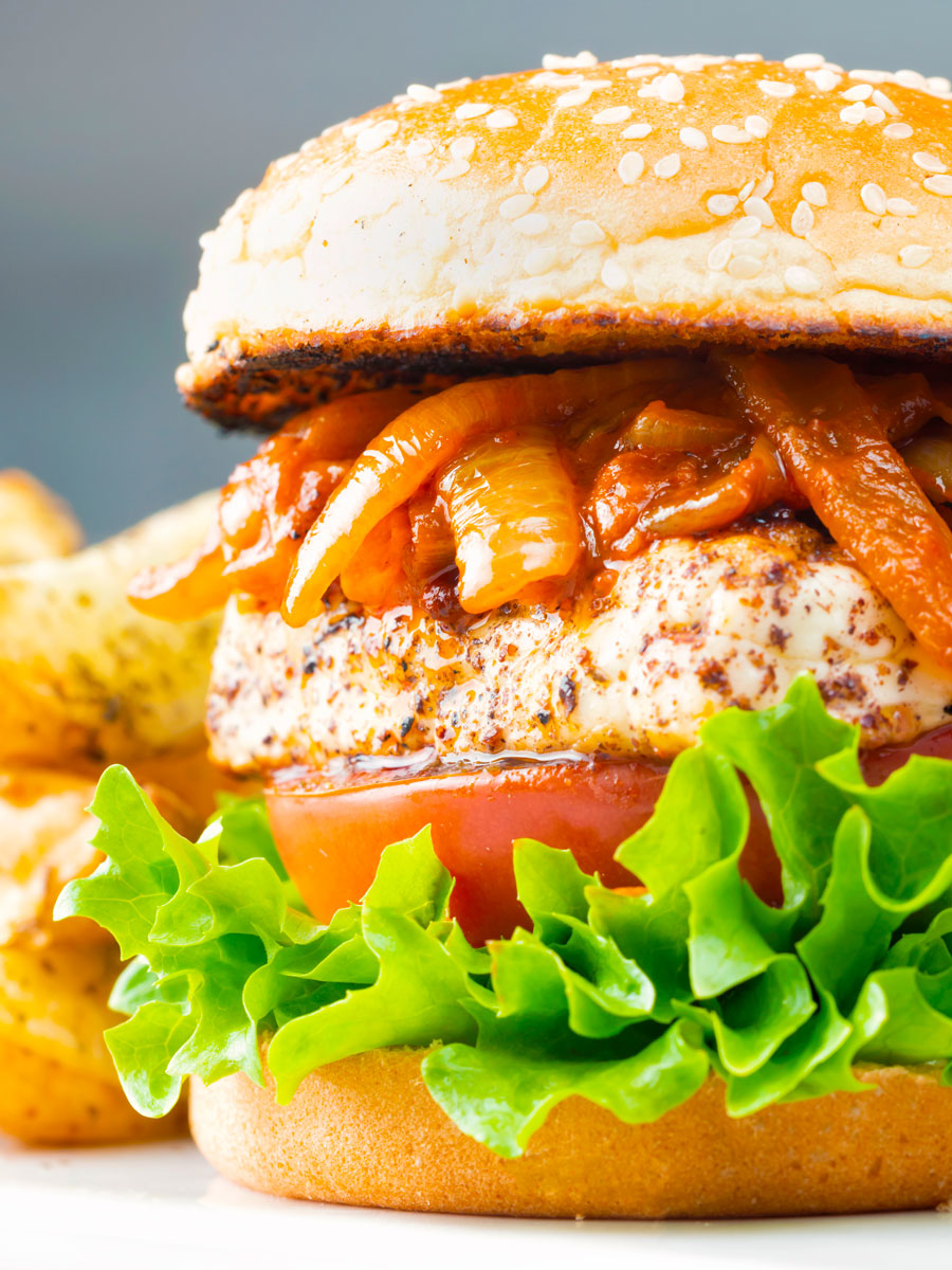 Halloumi burgers with harissa onions, tomato & lettuce on a sesame seed bun.