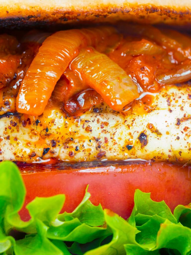Close up Halloumi burger with harissa onions, tomato & lettuce.
