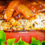 Close up Halloumi burger with harissa onions, tomato & lettuce featuring a title overlay.