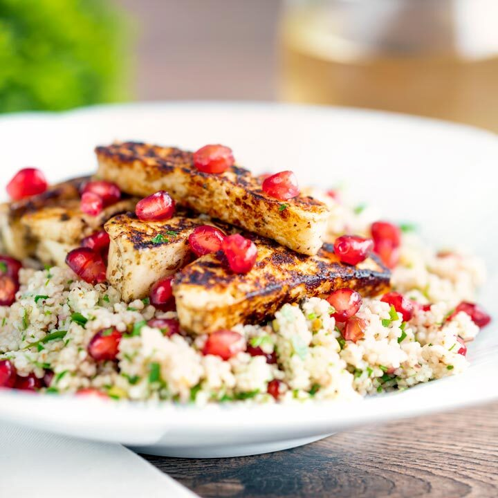 Seared zaatar halloumi cheese salad with pomegranate and couscous served in a white bowl.