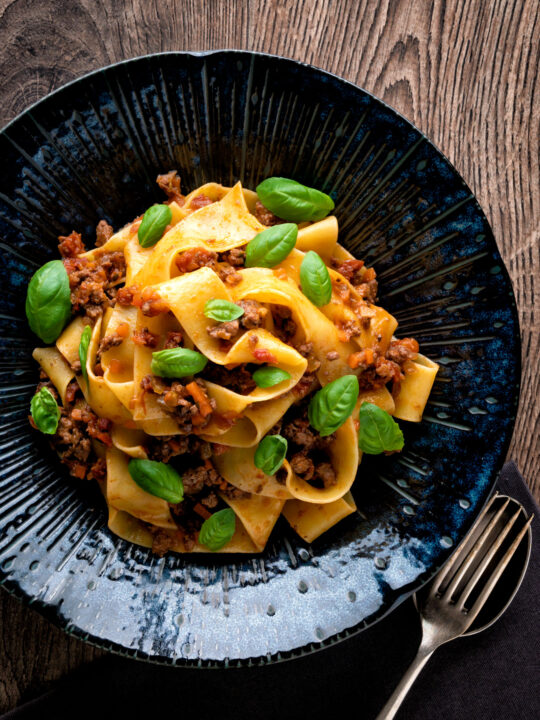 Over head Lamb ragu with pappardelle pasta and fresh basil.