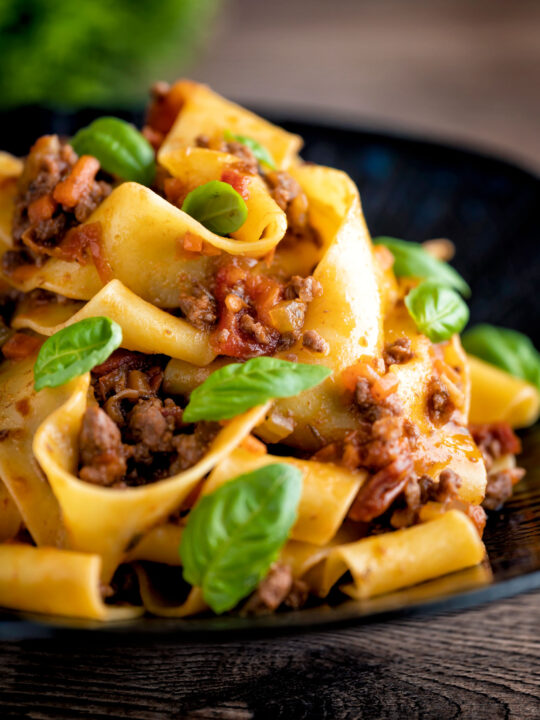 Lamb ragu with pappardelle pasta and fresh basil served on a dark blue plate.