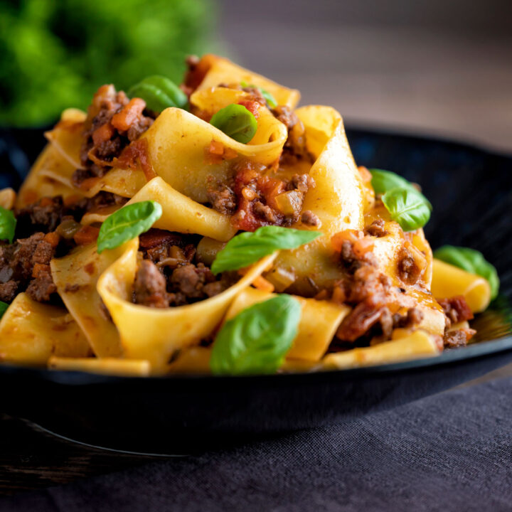 Minced lamb ragu with pappardelle pasta and fresh basil.