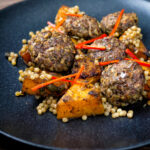 Mini lamb koftas served with roasted butternut squash and zaatar giant couscous featuring a title overlay.