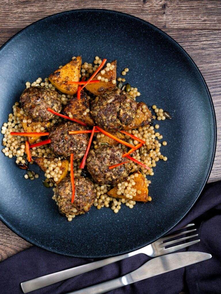 Overhead mini lamb koftas served with roasted butternut squash and zaatar giant couscous.
