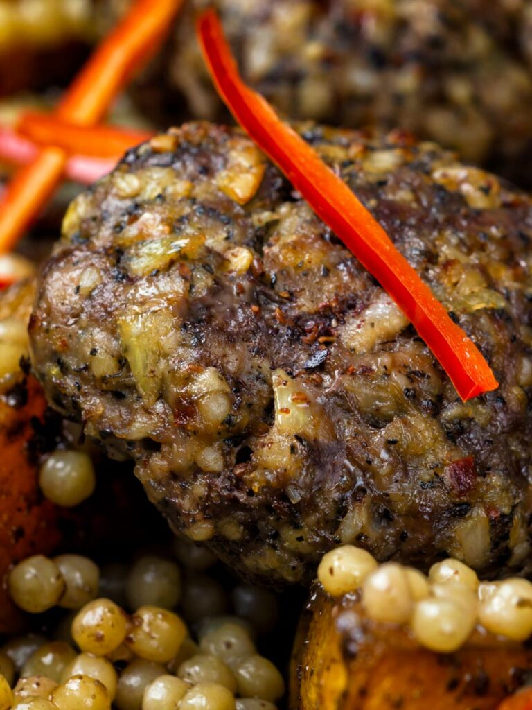 Close up lamb kofta served with roasted butternut squash and zaatar giant couscous.