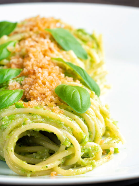 Peas pesto served as a sauce for pasta with a breadcrumb crust.
