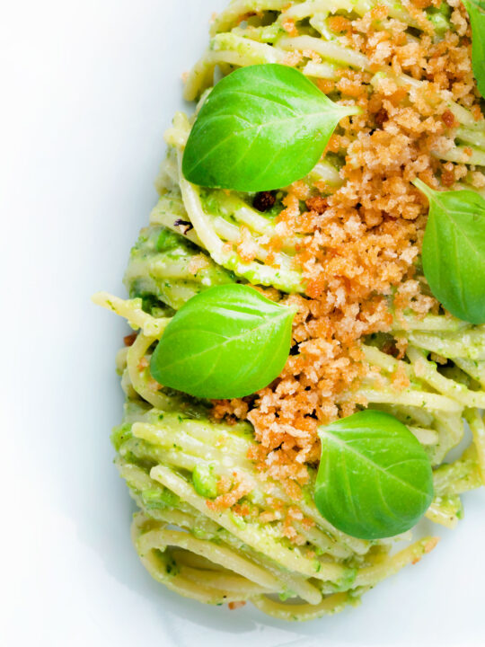 Overhead pea pesto served as a sauce for pasta with a breadcrumb crust.